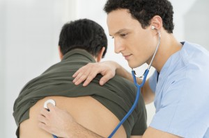 Young Male Doctor Checking Patient With Stethoscope In Hospital