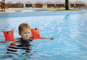 little boy having fun in the swimming pool of tropical resort